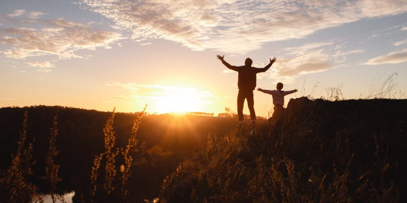 Silhouette of a free man and child enjoying freedom, feeling happy at sunset. Father and son on the edge of a cliff. Lifestyle